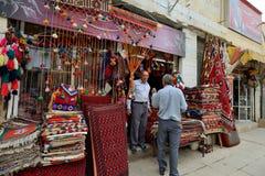 人在市场上换传统伊朗地毯 库存照片