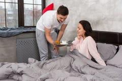 年轻人在床上带来了早餐,当他愉快的女朋友si时 库存照片