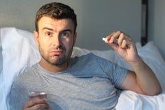 人在床上的采取一个药片 免版税库存照片