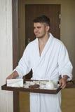 人在床上给妇女一份咖啡 乳酪蛋糕切片和咖啡 免版税库存图片