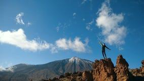 人在慢动作的一块大石头跳 在背景的泰德峰火山,特内里费岛,加那利群岛,西班牙 股票视频