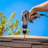 人在房子屋顶上把一个软的屋顶放 库存图片