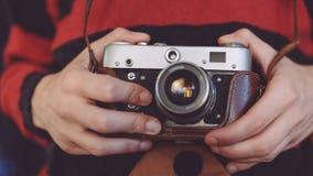 人在手上的拿着老减速火箭的照相机 免版税库存照片