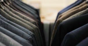 人在挂衣架的衣服夹克行  垂悬在挂衣架的新的美丽的衣裳的汇集在商店 股票视频
