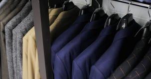 人在挂衣架的衣服夹克行  垂悬在挂衣架的新的美丽的衣裳的汇集在商店 影视素材