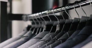 人在挂衣架的衣服夹克行  垂悬在挂衣架的新的美丽的衣裳的汇集在商店 股票录像