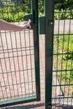 人在操场要到达通过被焊接的导线小的门  免版税库存图片