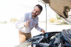 人在故障汽车附近的藏品量油计 库存图片