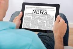 人在数字式片剂的读书报纸 免版税库存照片