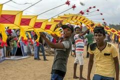 人在斯里兰卡帮助阻止日本风筝在之前离开在Negombo海滩 库存图片