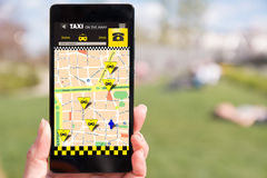人在智能手机的售票出租汽车,通过app 免版税库存照片
