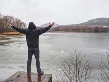 人在有上升的池塘测流堰站立他的手 免版税库存照片