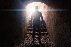 人在有发光的末端的黑暗的石隧道站立 免版税库存照片