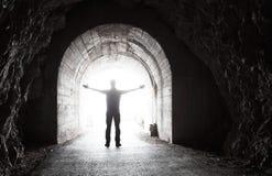 人在有发光的末端的黑暗的隧道站立 免版税库存照片