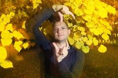 人在有奇怪的姿势的秋天公园 免版税库存图片