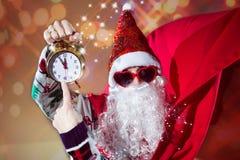 人在有时钟的圣诞老人服装 免版税库存照片