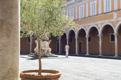 人在有穹顶和一个雕象的老庭院里,在比萨,意大利 库存图片