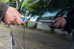 人在有螺丝刀的一辆汽车抓车门 库存照片