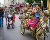 人在服装类似的儒勒・凡尔纳乘驾穿戴了他的在马瑞斯街道的周期  免版税图库摄影