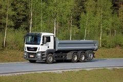 人在机动车路的翻斗卡车有森林背景 免版税图库摄影