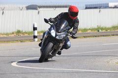 年轻人在柏油路曲线使用的骑马摩托车男性的a 免版税库存照片