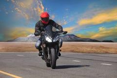 年轻人在柏油路曲线使用的骑马摩托车extrem的 免版税库存照片