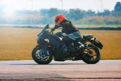 年轻人在柏油路曲线的骑马摩托车与与一mo 库存照片