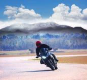 年轻人在柏油路的骑马摩托车反对山hig 免版税库存图片