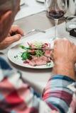 人在桌上在餐馆吃新鲜的沙拉用肉和蕃茄 免版税库存照片