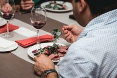 人在桌上在餐馆吃新鲜的沙拉用肉和蕃茄 免版税库存图片