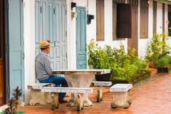 人在桌上坐一条城市街道在Louangphabang,老挝 特写镜头 复制文本的空间 图库摄影