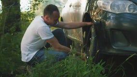 人在森林更换一辆汽车的残破的轮子 库存图片