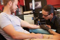 人在椅子有纹身花刺坐胳膊在客厅 图库摄影