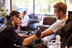 人在椅子有纹身花刺坐胳膊在客厅 免版税图库摄影