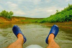 人在橡胶凉鞋的` s脚特写镜头在河的背景,室外活动的一艘筏 免版税库存图片