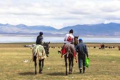 人在歌曲Kul湖骑马在吉尔吉斯斯坦 免版税库存照片