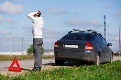 人在残破的汽车附近站立 免版税库存图片