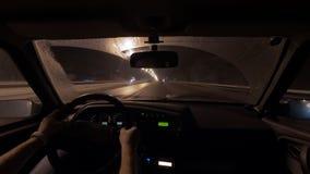 人在汽车位子并且乘坐在夜间在城市,看法在控制板和路坐 股票视频