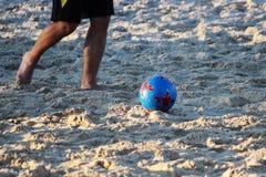 年轻人在沙子平台的夏天踢橄榄球 库存照片