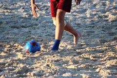 年轻人在沙子平台的夏天踢橄榄球 库存图片