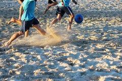 年轻人在沙子平台的夏天踢橄榄球 免版税库存照片