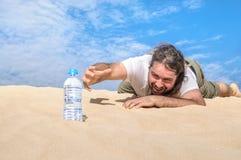 渴人在沙漠为一个瓶水到达 免版税库存照片
