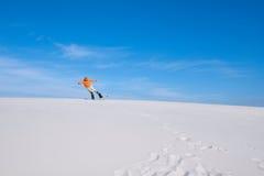 人在沙漠做在雪板的一个把戏 库存图片