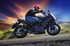年轻人在沥青乡下公路aga曲线的骑马摩托车  免版税图库摄影