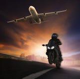 年轻人在沥青高速公路路的骑马摩托车有高s的 库存照片