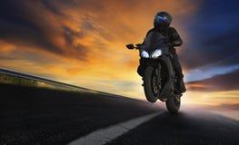 年轻人在沥青高速公路路的骑马摩托车有profes的 库存图片