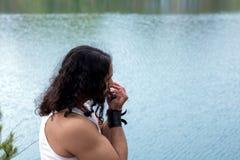 年轻人在河岸的口琴使用 免版税库存照片