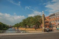 人在河有树、大厦和蓝天的里约Dommel的过桥,在s斯海尔托亨博斯 免版税库存照片
