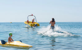 年轻人在波浪的滑水竞赛滑动在海,海洋 健康生活方式 正面人的情感,感觉,喜悦 免版税库存图片
