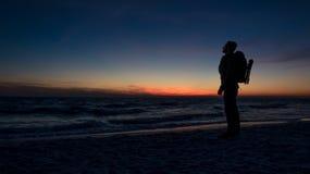 人在海洋的剧烈的日落前面站立 免版税库存图片